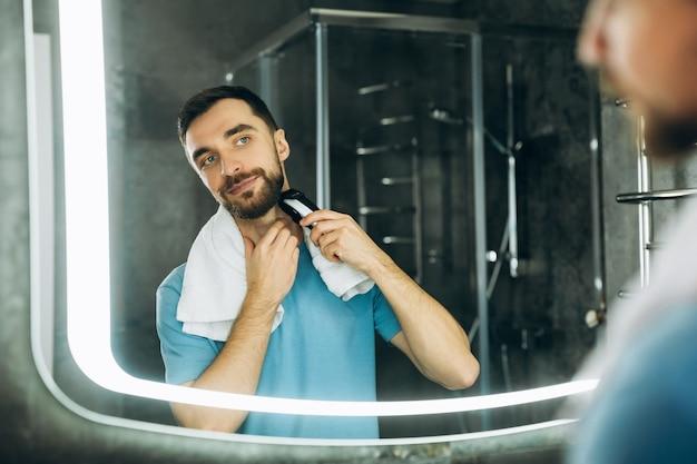 Junger gutaussehender mann mit handtuch, der den spiegel betrachtet und sich früh morgens zu hause rasiert