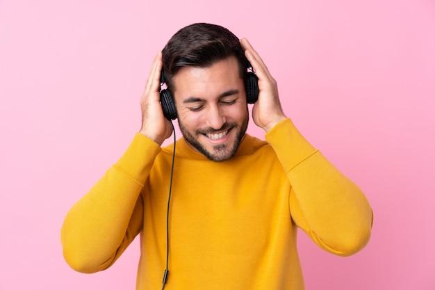 Junger gutaussehender mann mit hörender musik des bartes über lokalisierter rosa wand