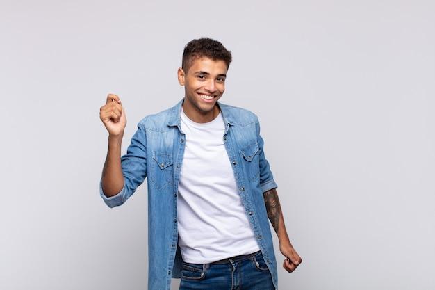 Junger gutaussehender mann mit jeanshemd posiert auf weißer wand