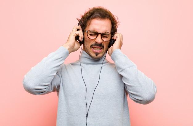 Junger gutaussehender mann mit kopfhörern gegen rosa flache wand