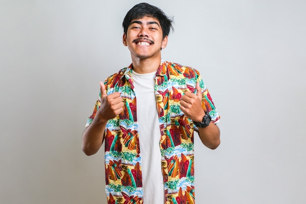 Junger gutaussehender mann mit lässigem hemd über weißem hintergrund, der positive gesten mit der hand genehmigt, daumen hoch lächelnd und glücklich über den erfolg. gewinner-geste.
