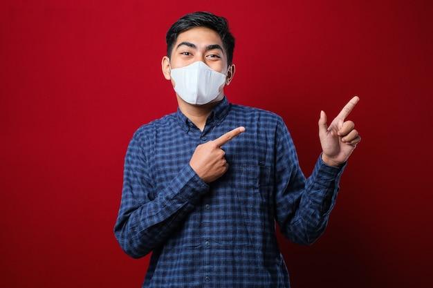 Junger gutaussehender mann mit medizinischer maske lächelt und schaut in die kamera, die mit einer hand und fingern auf die seite über rotem hintergrund zeigt
