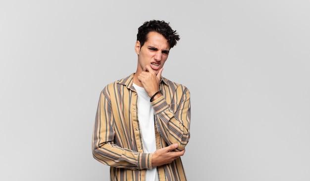 Junger gutaussehender mann mit offenem mund und weit geöffneten augen und hand am kinn, der sich unangenehm geschockt fühlt und sagt, was oder wow