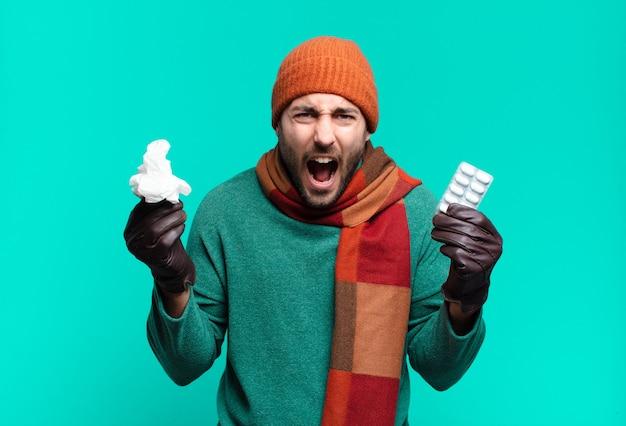 Junger gutaussehender mann mit pillentablette. krankheits-, grippe- oder hustenkonzept