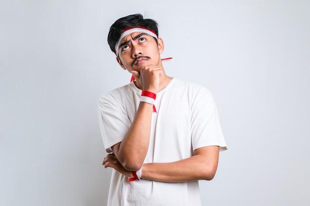 Junger gutaussehender mann mit rotem und weißem stirnband denkt besorgt über eine frage, besorgt und nervös mit der hand am kinn