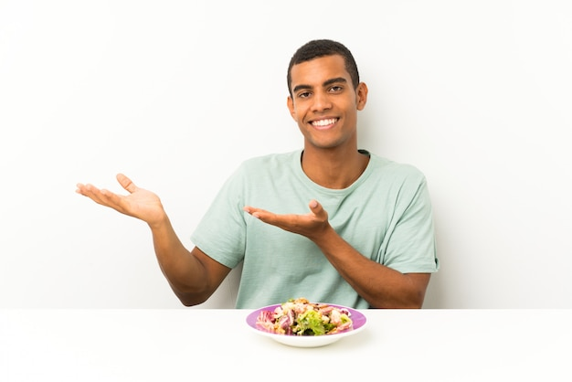 Junger gutaussehender mann mit salat in einer tabelle, die hände zur seite für die einladung ausdehnt, um zu kommen