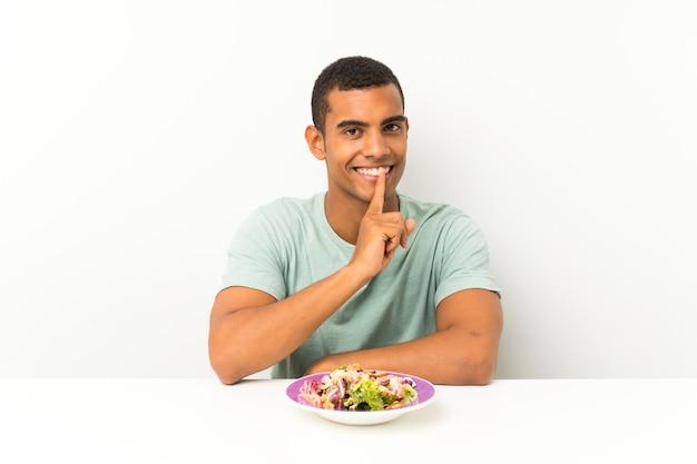 Junger gutaussehender mann mit salat in einer tabelle, die ruhegeste tut