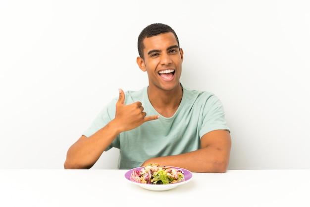 Junger gutaussehender mann mit salat in einer tabelle, die telefongeste macht