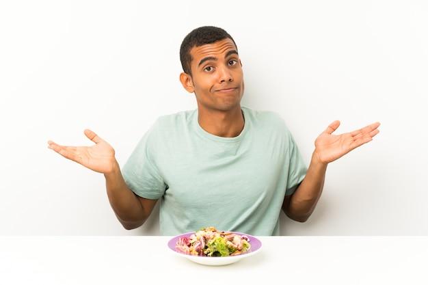 Junger gutaussehender mann mit salat in einer tabelle, die zweifel mit verwirren gesichtsausdruck hat