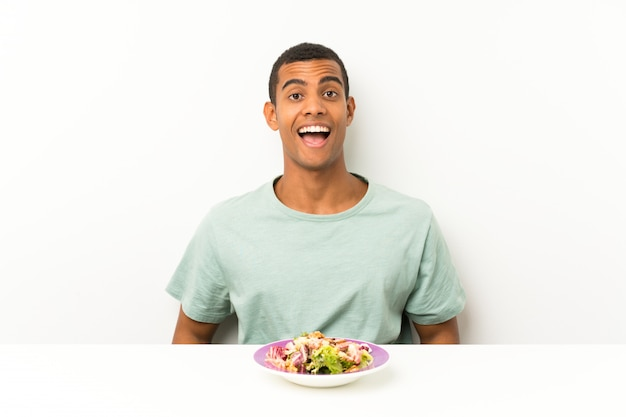 Junger gutaussehender mann mit salat in einer tabelle mit überraschungsgesichtsausdruck