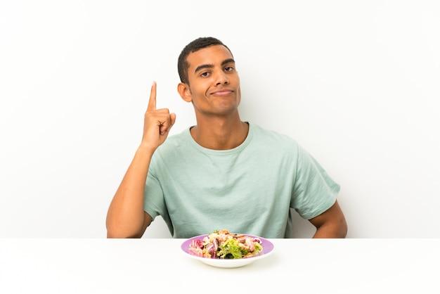 Junger gutaussehender mann mit salat in einer tabelle zeigend mit dem zeigefinger eine großartige idee