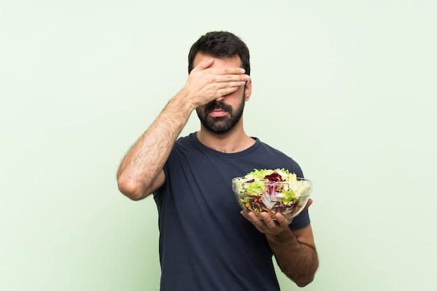 Junger gutaussehender mann mit salat über grüner wandverkleidung mustert durch hände. ich will nichts sehen