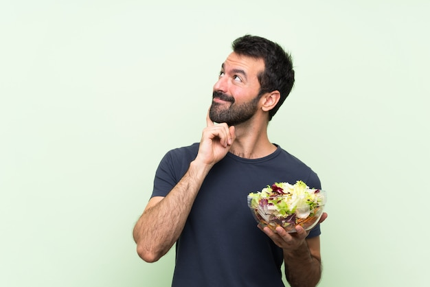 Junger gutaussehender mann mit salat über lokalisierter grüner wand eine idee beim oben schauen denkend