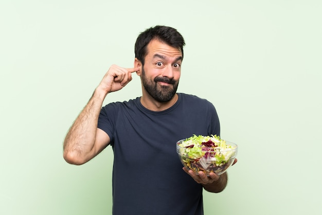 Junger gutaussehender mann mit salat über lokalisierter grüner wand frustrierte und bedeckungsohren