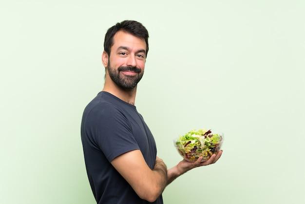 Junger gutaussehender mann mit salat über lokalisierter grüner wand mit den armen gekreuzt und vorwärts schauend