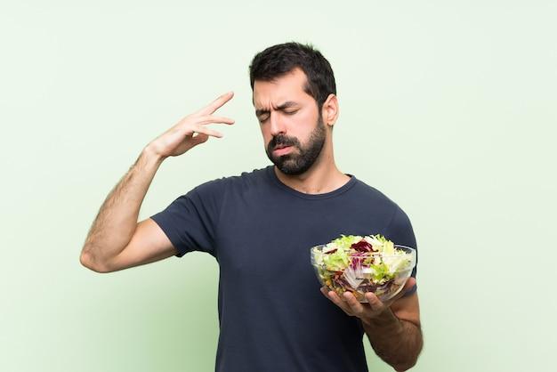Junger gutaussehender mann mit salat über lokalisierter grüner wand mit müdem und krankem ausdruck