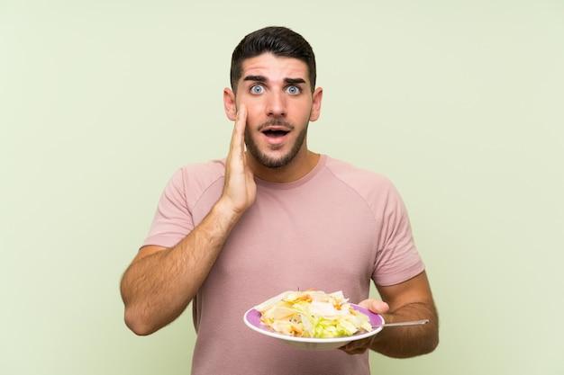 Junger gutaussehender mann mit salat über lokalisierter grüner wand mit überraschung und entsetztem gesichtsausdruck