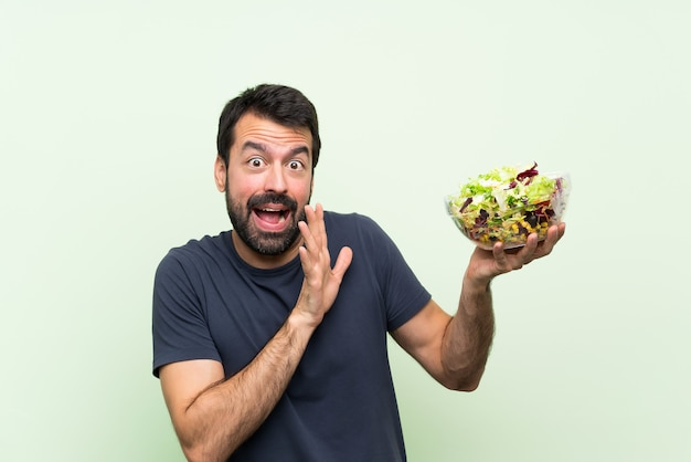 Junger gutaussehender mann mit salat über lokalisierter grüner wand nervös und erschrocken