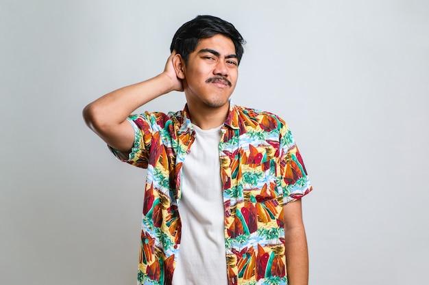Junger gutaussehender mann mit schnurrbart, der ein lässiges hemd trägt, das über weißem hintergrund steht, verwirren und wundern sich über die frage. unsicher im zweifel, denken mit der hand auf dem kopf. nachdenkliches konzept.