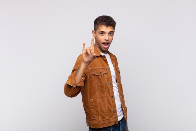 Junger gutaussehender mann mit schwermetallgeste Premium Fotos