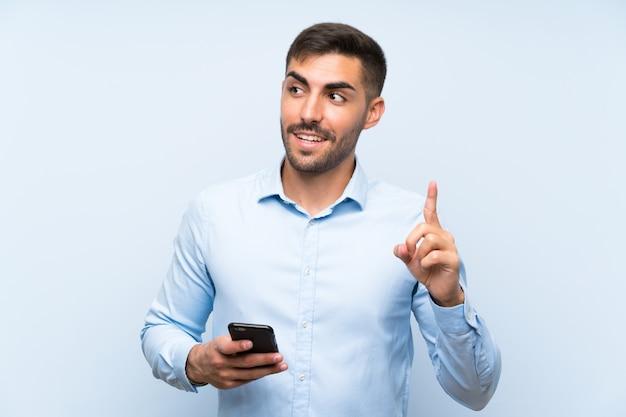 Junger gutaussehender mann mit seinem mobile über der lokalisierten blauen wand, die beabsichtigt, die lösung beim anheben eines fingers zu verwirklichen