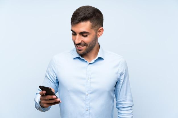 Junger gutaussehender mann mit seinem mobile über lokalisierter blauer wand viel lächelnd
