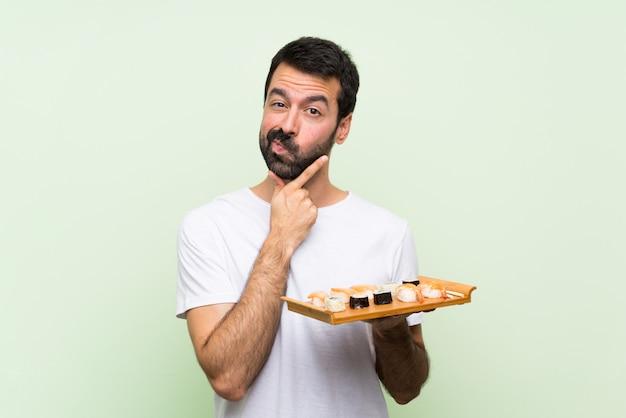 Junger gutaussehender mann mit sushi über lokalisiertem grünem wanddenken