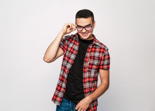 Junger gutaussehender mann mit tragenden modebrillen des großen lächelns