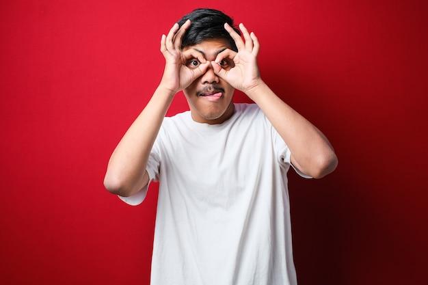 Junger gutaussehender mann mit weißem t-shirt, der eine ok geste macht, wie ein fernglas, das die zunge herausstreckt, die augen durch die finger schauen. verrückter ausdruck auf rotem hintergrund