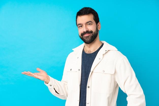 Junger gutaussehender mann mit weißer cordjacke, die eine idee beim lächeln lächelnd darstellt