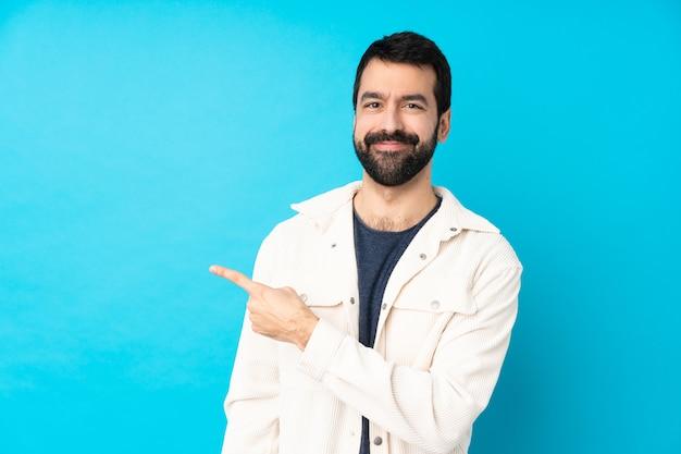 Junger gutaussehender mann mit weißer cordjacke über blau, das zur seite zeigt, um ein produkt zu präsentieren