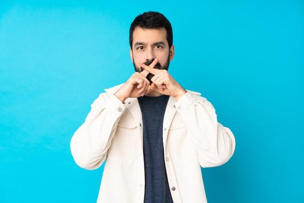 Junger gutaussehender mann mit weißer cordjacke über blau, die ein zeichen der stille geste zeigt