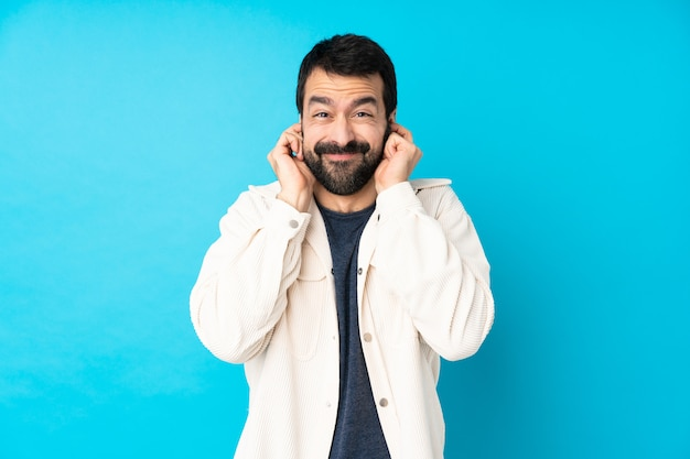 Junger gutaussehender mann mit weißer cordjacke über blau frustrierten und bedeckenden ohren