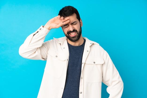 Junger gutaussehender mann mit weißer cordjacke über blau mit müde und krankem ausdruck