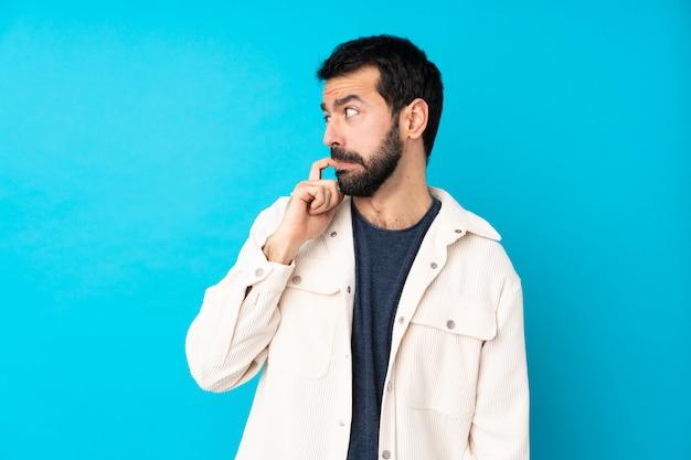Junger gutaussehender mann mit weißer cordjacke über blau nervös und verängstigt