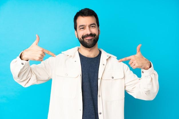 Junger gutaussehender mann mit weißer cordjacke über blau stolz und selbstzufrieden