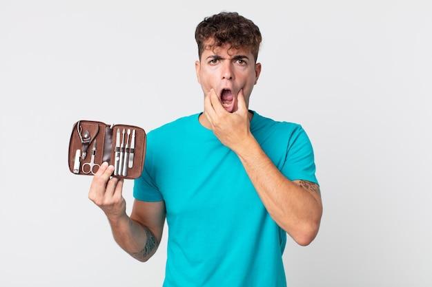 Junger gutaussehender mann mit weit geöffnetem mund und augen und hand am kinn und hält einen nagelwerkzeugkoffer