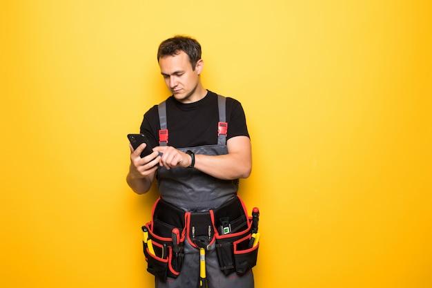 Junger gutaussehender mann mit werkzeuggürtel verwenden mobiltelefon