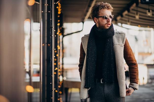 Junger gutaussehender mann mit winterkleidung gehend auf straße
