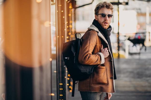 Junger gutaussehender mann mit winterkleidung und -rucksack