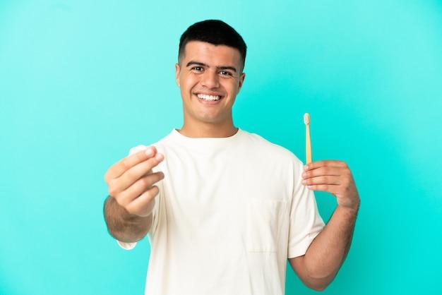 Junger gutaussehender mann putzt sich die zähne über isoliertem blauem hintergrund und macht geldgeste