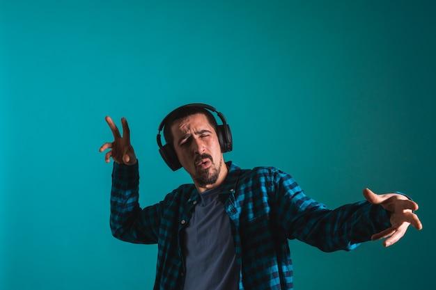 Junger gutaussehender mann tanzt und singt lieder, die musik über kopfhörer auf blauem hintergrund hören
