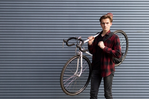 Junger gutaussehender mann trägt ein kaputtes fahrrad auf den schultern an der wand, der student geht zu fuß