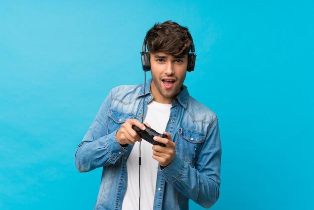 Junger gutaussehender mann über dem lokalisierten blau, das an den videospielen spielt