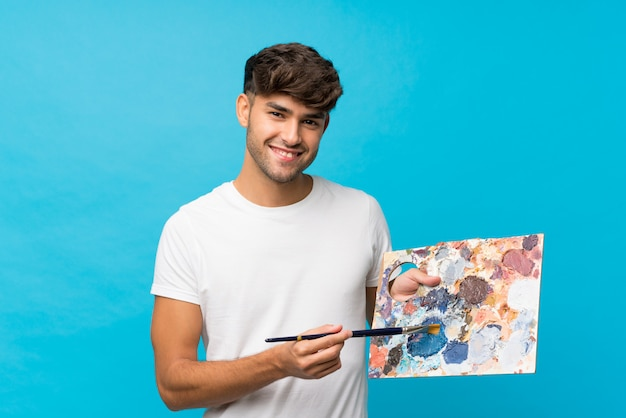 Junger gutaussehender mann über dem lokalisierten blau, das eine palette hält