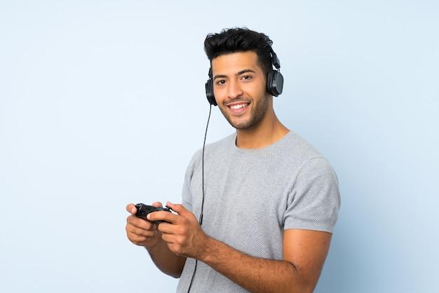 Junger gutaussehender mann über dem lokalisierten hintergrund, der an den videospielen spielt