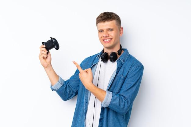 Junger gutaussehender mann über dem lokalisierten weiß, das an den videospielen spielt