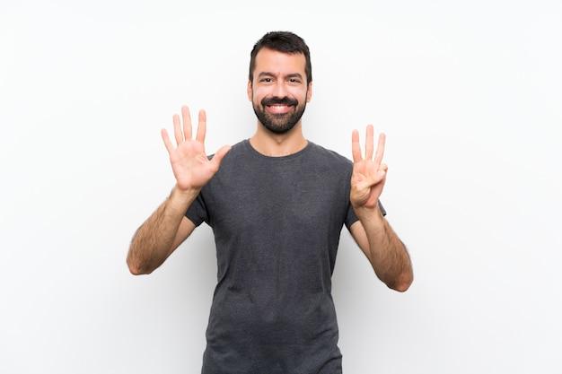 Junger gutaussehender mann über dem lokalisierten weißen hintergrund, der acht mit den fingern zählt