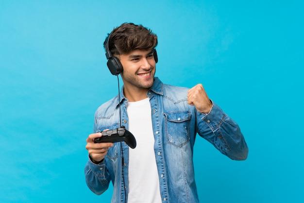 Junger gutaussehender mann über der lokalisierten blauen wand, die an den videospielen spielt