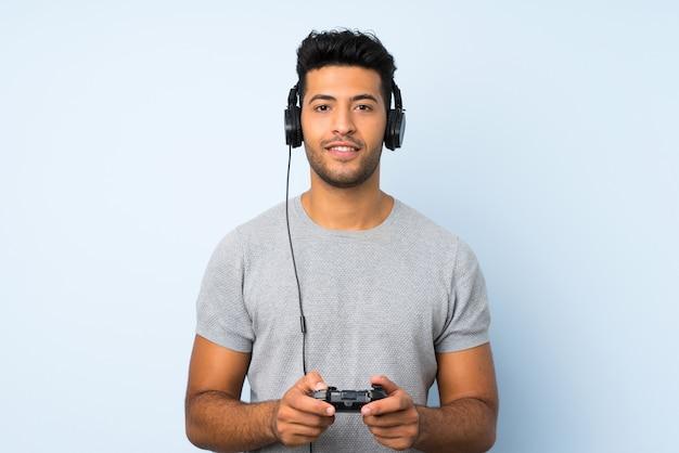Junger gutaussehender mann über der lokalisierten wand, die an den videospielen spielt